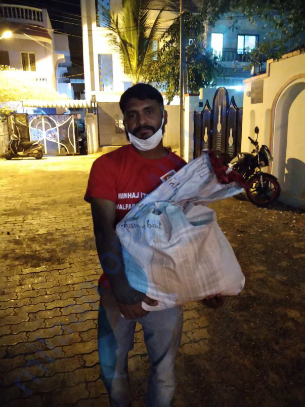 Brother Tahir distributing the food packets to needy families