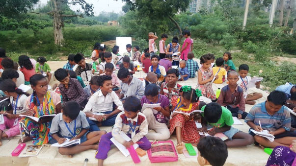 Children studying Roadside in open.