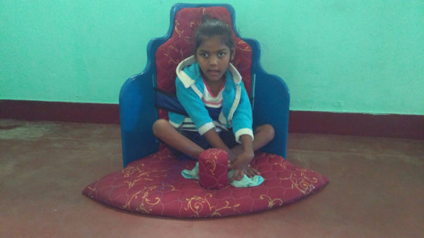 Cerebralpalsy child getting trained for her hip balance in corner seat