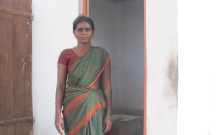 Anitha pictured beside the toilet constructed with her microloan
