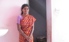 Rajalakshmi pictured beside her toilet constructed with the help of a microloan