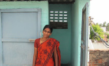 Bhuvaneshari is pictured here beside the toilet she constructed with the assistance of a microloan