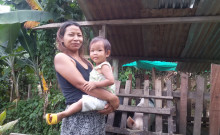 Vanlalnguri carrying her daughter and standing in front of their backyard piggery.