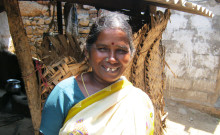 Tamilrasi standing in front of her house