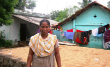 Suganya standing in front of the base of her new house