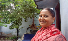 Shailaja standing beside her house