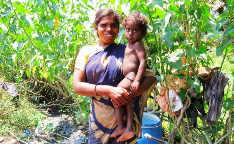 Radhiga standing near her water pipe and tank