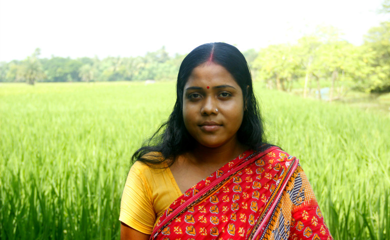 Kalpana stands next to her field