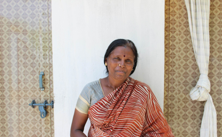Jayakodi next to her home's toilet