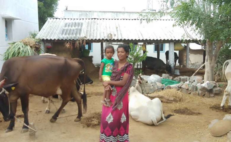 Sathiya with her son and the cows in the background