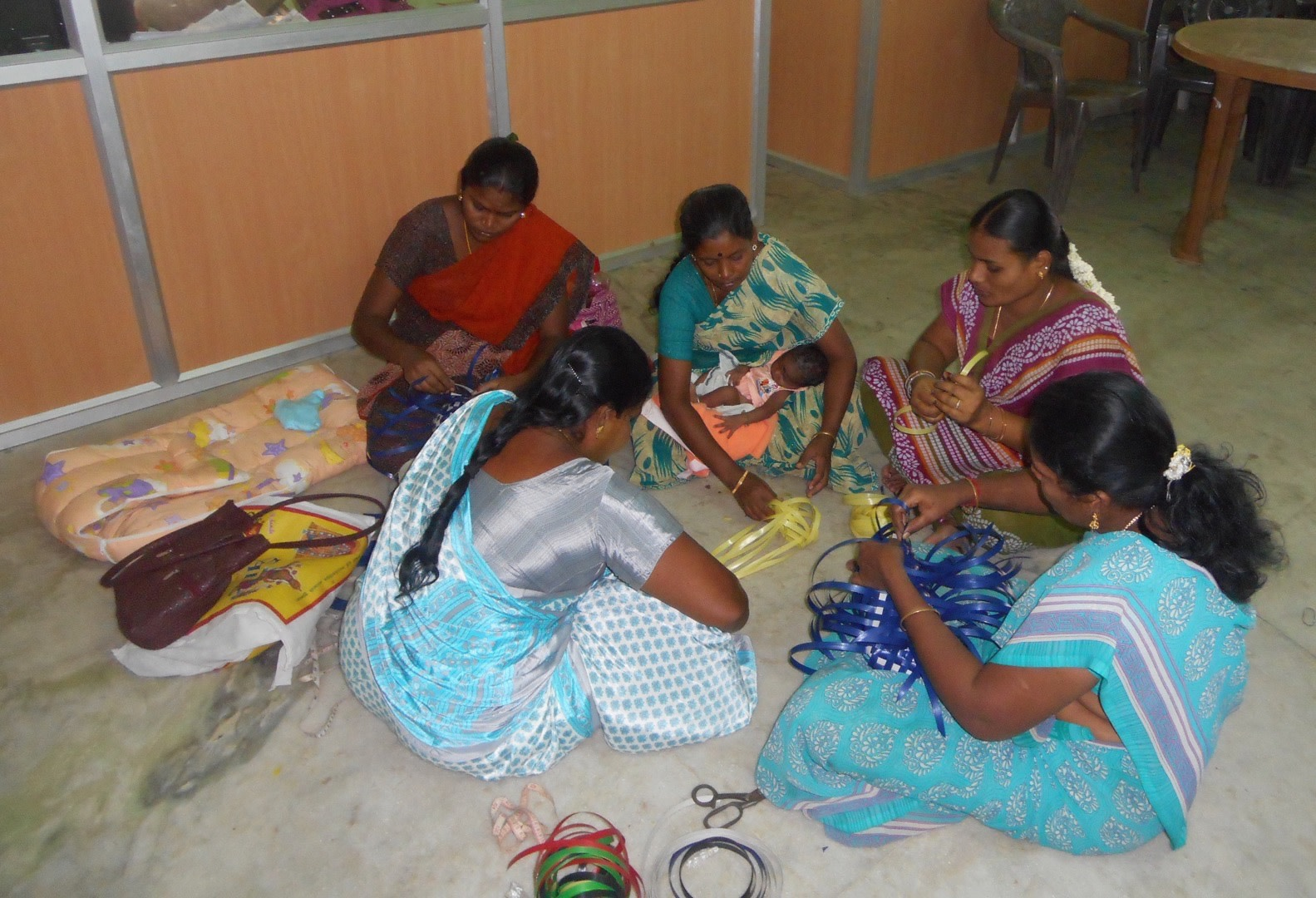 A group of aspiring entrepreneurs learning the skill of making wire bags