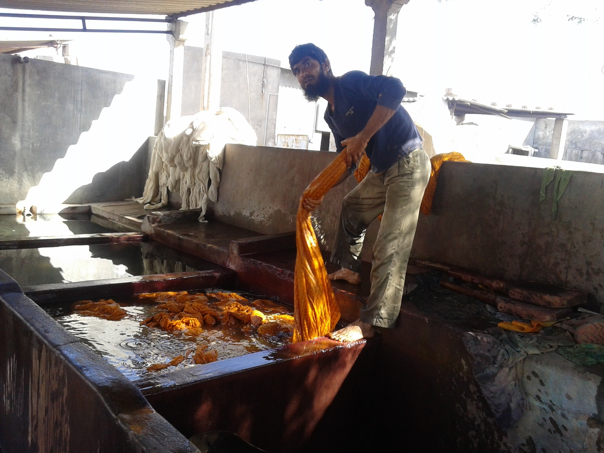 A worker dyeing dress materials in a textile industry