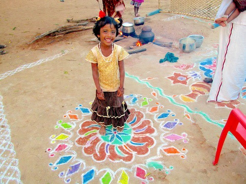 A proud girl stands over her kolam