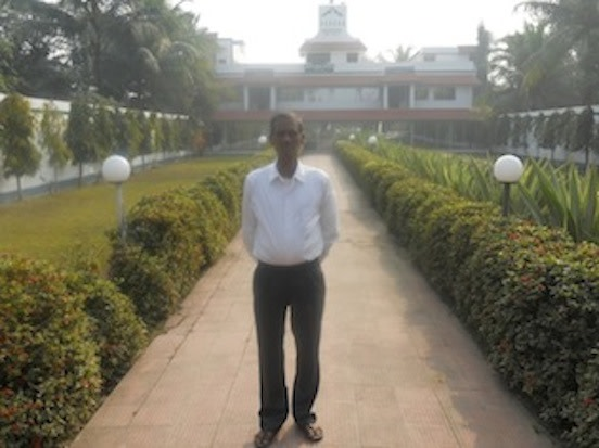 Kapilana Mondal in front of VSSU's headquarters and guesthouse.