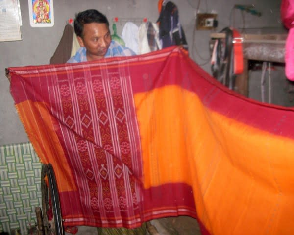 A weaver with a finished sari.