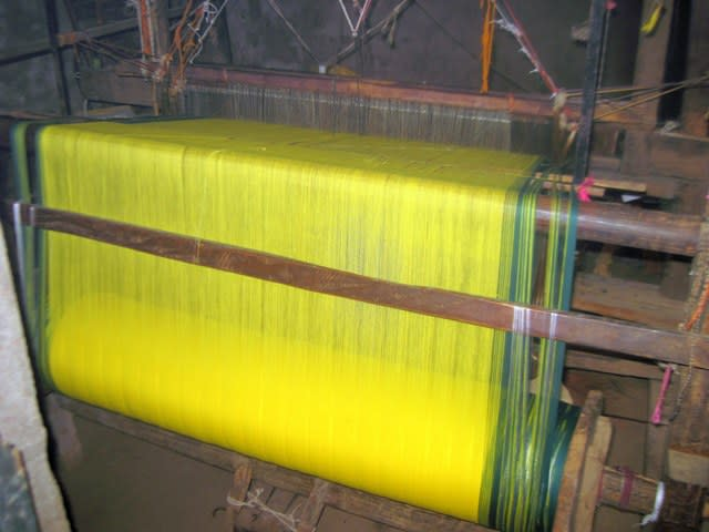 A warp beam loaded on the handloom with warp held in tension. Also, warp ends passing through eyes holes of the heddles may be observed.