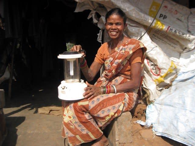 Ms. Himarika Santi with solar lantern outside her house