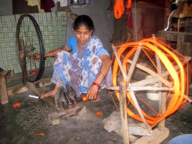 A weaver working on the charkha to create thread yarn to be used as weft.