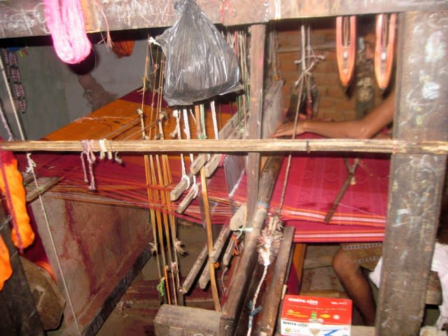 The raised warp ends passing through the heddles and the shed created is seen clearly in this picture.