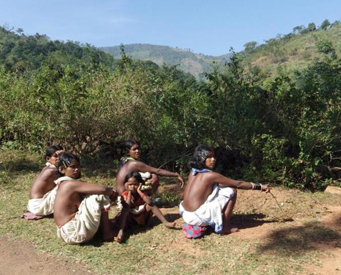 Tribal women taking rest alongside a road
