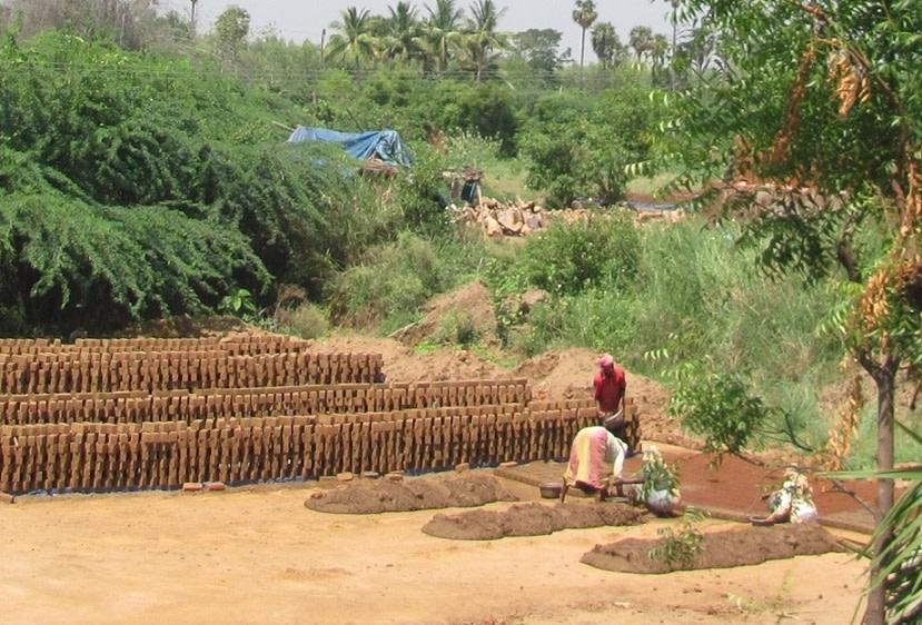 Workers arrange bricks at a brick kiln