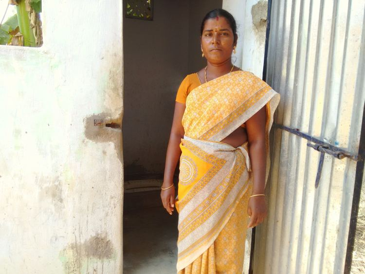 Murugavalli stands outside her newly constructed toilet