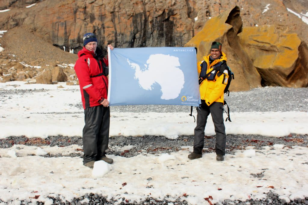 On the main land of Antarctica with Jonathan Shackleton and the Antarctic flag