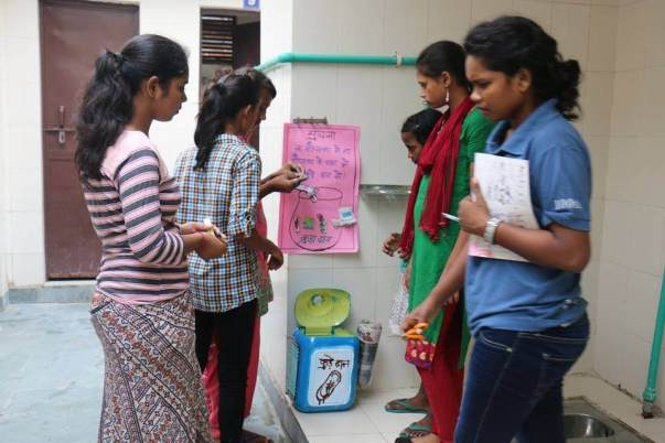Dustbins made by girls at the Lab being installed in the community
