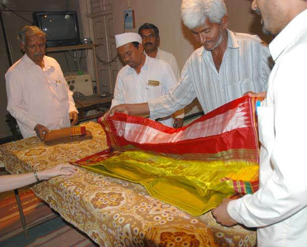 Weavers showing a foreigner the varieties of saris stored.