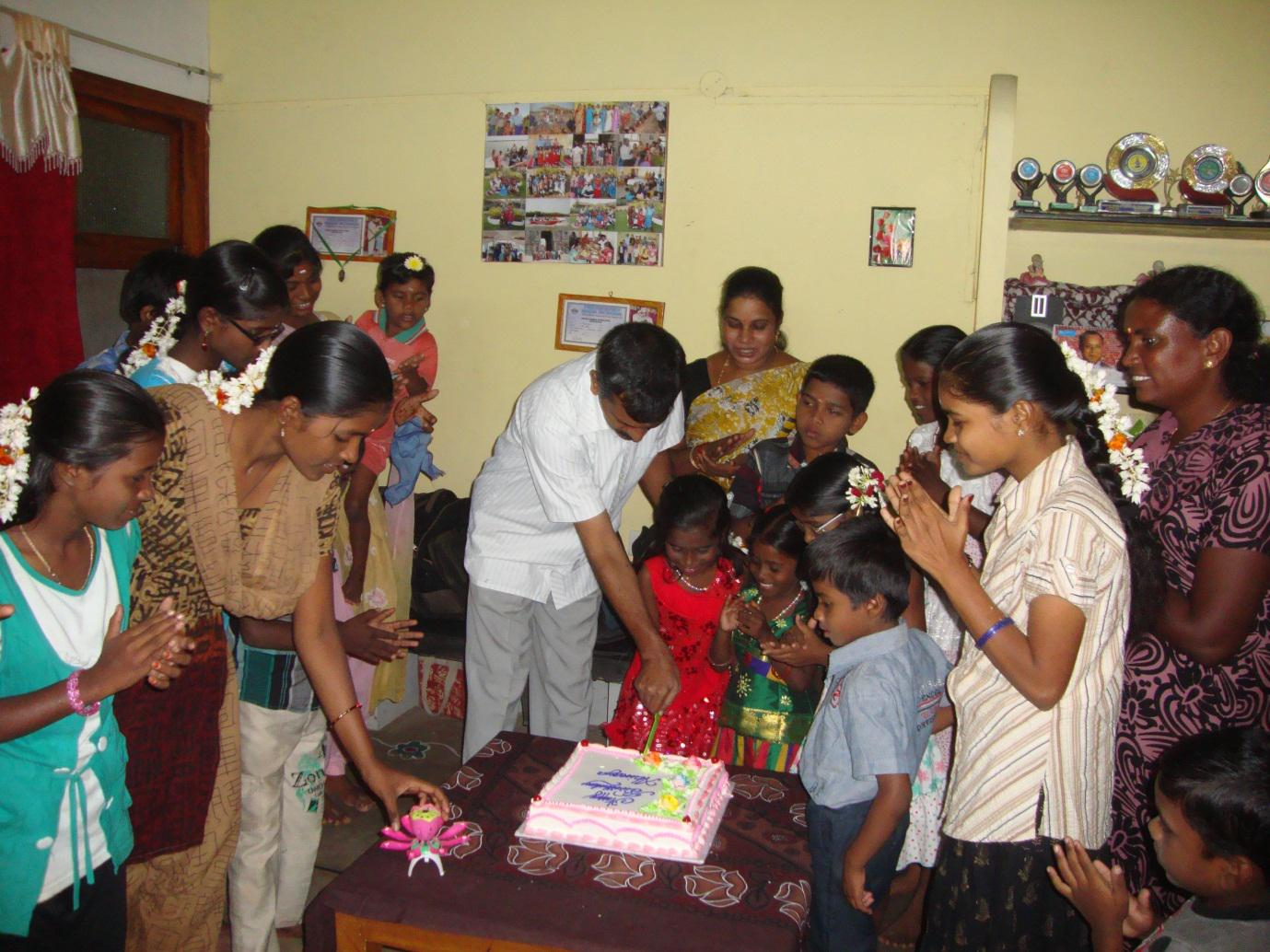 Ananya cutting her birthday cake along with her SOS family