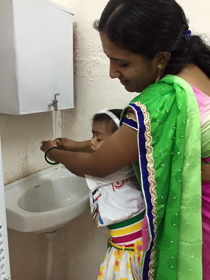Teacher helping in handwash